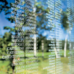 Close-up photograph of engraved names of individuals on a large glass plaque