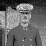 Black and white photograph of a man in a naval uniform standing on the porch of a building
