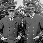 Black and white photograph of two men in naval uniforms standing outside