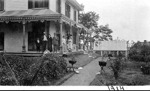 Black and white photograph of a group of people standing on the porch of a large house