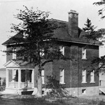 Black and white photograph of a brick house and several trees