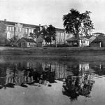 Black and white photograph of several buildings seen from the water