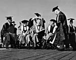 Black and white photograph of Winston Churchill and Franklin D. Roosevelt and others, in university robes and graduation caps, receiving honorary degrees.