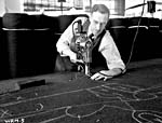 Black and white photograph of a tailor cutting out pattern pieces on a large table.  Bolts of fabric are behind him.