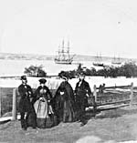 Photograph of two men and two women in front of ships HMS NILE, NIMBLE, and DESPERATE, Halifax, Nova Scotia, circa 1860