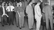 Photograph of men waiting in line to vote, June 1957