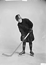 Photograph of Eva Ault, wearing skates and holding a hockey stick, 1917