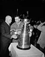 Photograph of Stanley Cup trustee Cooper Smeaton presenting the trophy to Maurice Richard, April 16, 1957
