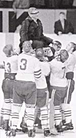 Photograph of Arne Stromberg being carried upon the shoulders of his players