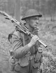 Photoghraph of a soldier carrying machine gun.