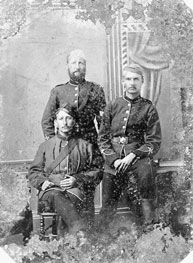 Photograph of three men sitting together for portrait.