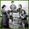 Group of female workers enjoying a break from their work of packing crates of 25-pounder field gun cases at a munitions plant (prob. Robert Mitchell Co.)