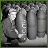 Workman smiles and writes 'ADOLF' in chalk on the body of a bomb at the Cherrier plant