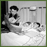 Mrs. Jack Wright reads her two sons Ralph and David a bed-time story