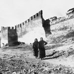 two women walking past a damaged ancient city wall with turrets and guard towers.