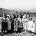 Local women and children pose for a photograph, woman on far left is spinning wool.