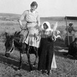 Nursing sister sitting sidesaddle on a donkey and a local woman standing next to her spinning wool