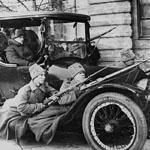 Soldats russes en uniforme perchés sur une automobile avec leur fusil à la main