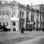 Vue du palais transformé en bâtiment de l'hôpital en temps de guerre. Les voitures et les piétons circulent dans les rues.