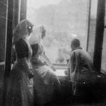 Soldat, qui est dans une chaise roulante, et deux soeurs infirmières. Les trois sont assises proche de la fenêtre, et observent ce qui se passe dans la rue.