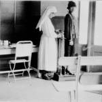 Femme debout sur une échelle tandis que la soeur infirmière adapte l'appareil.