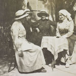 Three women in large brimmed hats and a nursing sister at a table surrounded by palm trees