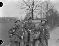 Photograph of three photographers of the Canadian Army Film and Photo Unit attached to the 1st Canadian Parachute Battalion. Wissel, Germany, March 27, 1945. Photograph by Lieutenant Barney J. Gloster