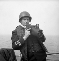 Photograph of Lieutenant Gilbert A. Milne of the Royal Canadian Naval Volunteer Reserve, holding a Fairchild K20 camera. England, June 2, 1944. Photograph by Lieutenant Richard G. Arless