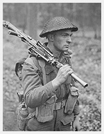 Photograph of Private H.E. Goddard of The Perth Regiment, carrying a Bren gun while advancing through a forest north of Arnhem, Netherlands, April 15, 1945. Photograph by Captain Jack H. Smith.