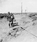 Photograph of two Canadians carrying German helmets, walking along a road, near Courcelette, October 1916