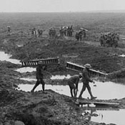 Canadian pioneers carrying trench mats with wounded and prisoners in background during the Battle of Passchendaele