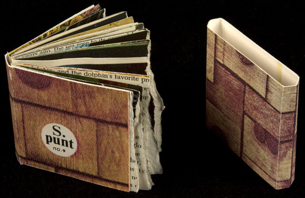 On the left, a book is upright and open; on the bottom left of its cover is a white circle with black print in the centre. On the right, a slipcase is upright. The book cover and slipcase are brown with thick dark brown vertical and horizontal lines, forming a block pattern.