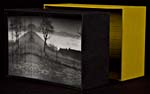 In the background, a yellow rectangular cardboard box is standing upright with black print that can be seen on the interior. In the foreground on the left, emerging from the yellow box, is a black rectangular box with a black and white photograph of some houses, trees, clouds, and a mountain range in the background.