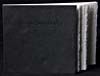 Book standing upright and slightly fanned out with black cover, title printed in black on the top right of the cover and white textured page edges.