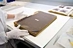 Photograph of a conservator carefully handling the worn and detached covers of a counter book