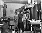 Photograph of Mrs. Bluett and daughter Margaret washing dishes for the last time in their old Toronto home, scheduled for slum clearance project, circa 1949