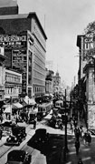 Black-and-white photograph of a busy street scene with pedestrians, cars and streetcars. Buildings in the background have prominent signs on them