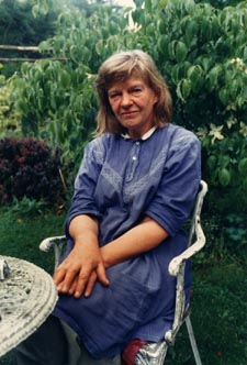 Photograph of Elizabeth Smart seated at a table in her garden, 1980