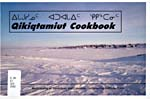Cover of cookbook, QIKIQTAMIUT COOKBOOK, featuring a photograph of a northern community on a snow-covered tundra