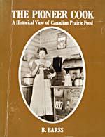 Cover of cookbook, THE PIONEER COOK: A HISTORICAL VIEW OF CANADIAN PRAIRIE FOOD, with an oval photograph of a pioneer woman standing beside a wood cooking stove and grinding coffee in a mill