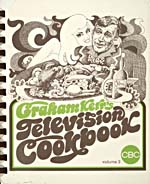 Cover of cookbook, GRAHAM KERR'S TELEVISION COOKBOOK, with a caricature-style drawing of a man, probably Graham Kerr, carrying a tray of food while a woman hugs him