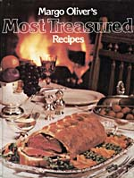 Cover of cookbook, MARGO OLIVER'S MOST TREASURED RECIPES, with a photograph of a table set with silver dishes containing various foods, while a fire burns in the background