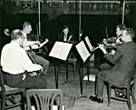 Photograph of Glenn Gould, facing a string quartet on stage in an empty hall
