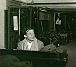 Photograph of Glenn Gould playing the piano backstage, with Philadelphia Orchestra trunks in the background