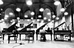 Photograph of Glenn Gould playing one of four grand pianos that are lined up side by side
