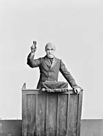 Photograph of Sergeant Ted Charter, The Dumbells' assistant manager, standing at a lectern