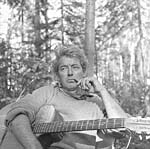 Photograph of Félix Leclerc in the woods, with his guitar