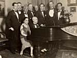Photograph of Éva Gauthier and Maurice Ravel seated at a piano, with several people standing behind them, at a party hosted by Gauthier for Ravel's birthday, March 7, 1928