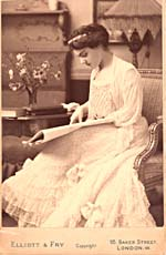 Photograph of Éva Gauthier in an evening gown, seated and reading a large score or newspaper, circa 1905