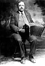 Photo d'Alfred Montmarquette, assis, tenant son accordéon